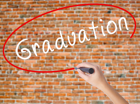 Woman Hand Writing Graduation with black marker on visual screen. Isolated on bricks. Business concept. Stock Photo