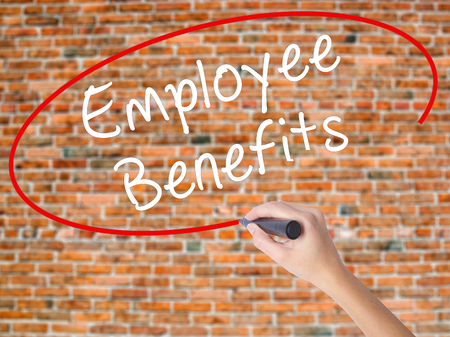 Woman Hand Writing Employee Benefits with black marker on visual screen. Isolated on bricks. Business concept. Stock Photo Stock Photo