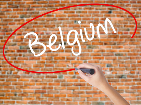 Woman Hand Writing Belgium  with black marker on visual screen. Isolated on bricks. Business concept. Stock Photo