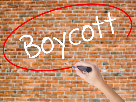 denying: Woman Hand Writing Boycott with black marker on visual screen. Isolated on bricks. Business concept. Stock Photo Stock Photo