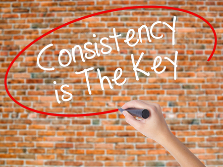 Woman Hand Writing Consistency is The Key with black marker on visual screen. Isolated on bricks. Business concept. Stock Photo Stock Photo