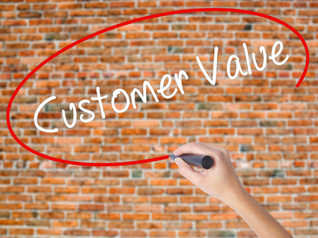 Woman Hand Writing Customer Value with black marker on visual screen. Isolated on bricks. Business concept. Stock Photo
