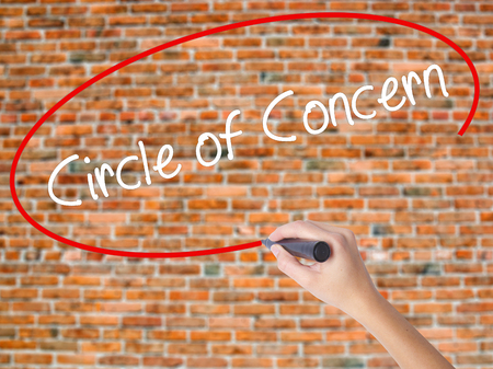 Woman Hand Writing Circle of Concern with black marker on visual screen. Isolated on bricks. Business concept. Stock Photo