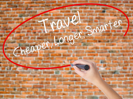 Woman Hand Writing Travel Cheaper Longer Smarter  with black marker on visual screen. Isolated on bricks. Business concept. Stock Photo Stock Photo