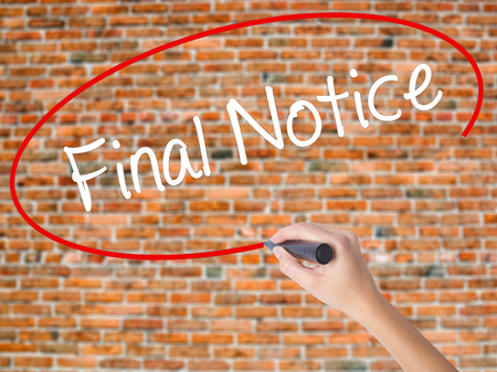 Woman Hand Writing Final Notice with black marker on visual screen. Isolated on bricks. Business concept. Stock Photo