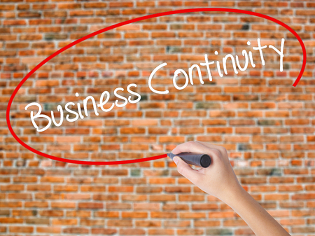 Woman Hand Writing Business Continuity with black marker on visual screen. Isolated on bricks. Business concept. Stock Photo Stock Photo