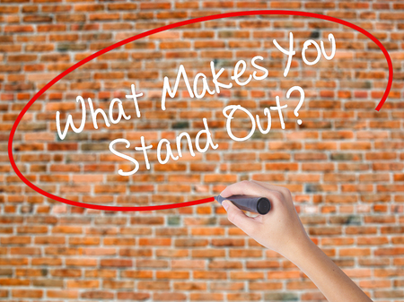 Woman Hand Writing What Makes You Stand Out? with black marker on visual screen. Isolated on bricks. Business concept. Stock Photo Stock Photo