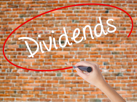 dividend: Woman Hand Writing Dividends with black marker on visual screen. Isolated on bricks. Business concept. Stock Photo