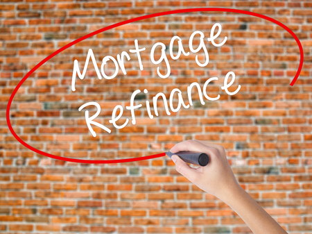 Woman Hand Writing Mortgage Refinance with black marker on visual screen. Isolated on bricks. Business concept. Stock Photo