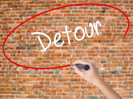 Woman Hand Writing Detour  with black marker on visual screen. Isolated on bricks. Business,  internet concept. Stock Photo