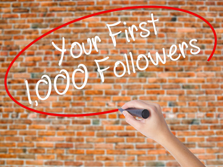 Woman Hand Writing Your First 1,000 Followers  with black marker on visual screen. Isolated on bricks. Business concept. Stock Photo