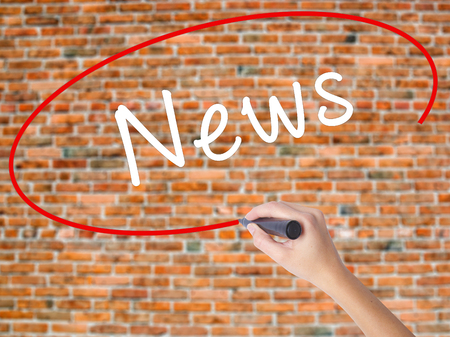 Woman Hand Writing News with black marker on visual screen. Isolated on bricks. Business concept. Stock Photo
