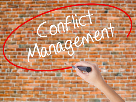 Woman Hand Writing Conflict Management with black marker on visual screen. Isolated on bricks. Business concept. Stock Photo