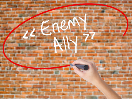 interdependence: Woman Hand Writing Enemy - Ally with black marker on visual screen. Isolated on bricks. Business concept. Stock Photo