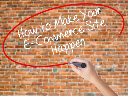 b2b: Woman Hand Writing How to Make Your E-Commerce Site Happen with black marker on visual screen. Isolated on bricks. Business concept. Stock Photo Foto de archivo