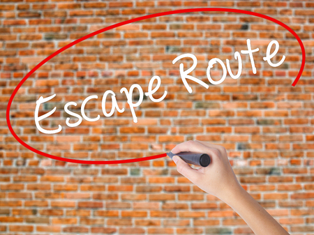 breakout: Woman Hand Writing Escape Route with black marker on visual screen. Isolated on bricks. Business concept. Stock Photo