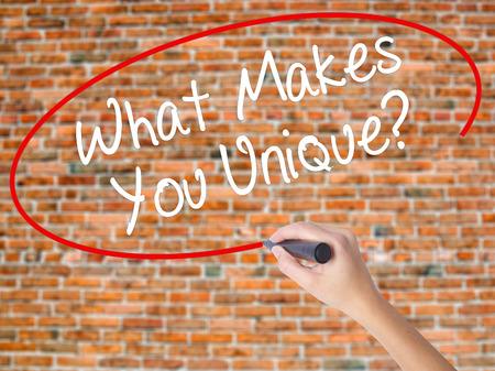 Femme main qui écrit Qu'est-ce qui vous rend unique? avec marqueur noir sur l'écran visuel. Isolé sur des briques. Concept d'affaires Photo en stock