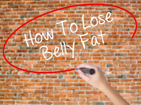 Woman Hand Writing How To Lose Belly Fat with black marker on visual screen. Isolated on bricks. Business concept. Stock Photo