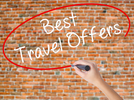Woman Hand Writing Best Travel Offers  with black marker on visual screen. Isolated on bricks. Travel technology, internet concept. Stock Image Stock Photo