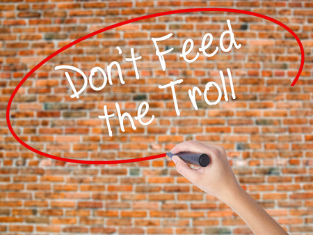 Woman Hand Writing Dont Feed the Troll with black marker on visual screen. Isolated on bricks. Business concept. Stock Photo