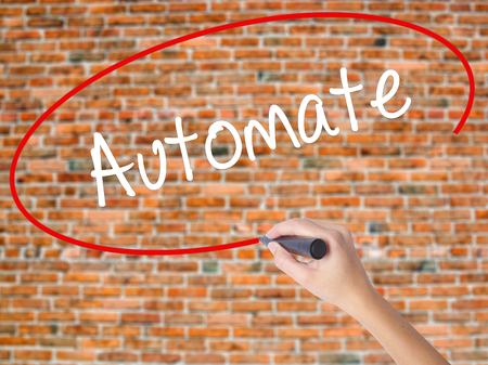 Woman Hand Writing Automate with black marker on visual screen. Isolated on bricks. Business concept. Stock Photo Stock Photo