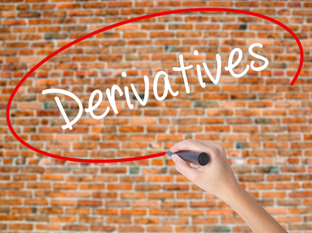 Woman Hand Writing Derivatives with black marker on visual screen. Isolated on bricks. Business concept. Stock Photo