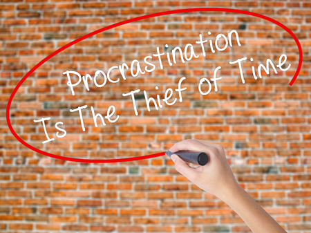 Woman Hand Writing  Procrastination Is The Thief of Time with black marker on visual screen. Isolated on bricks. Business concept. Stock Photo
