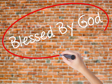 preachment: Woman Hand Writing Blessed By God with black marker on visual screen. Isolated on bricks. Business concept. Stock Photo