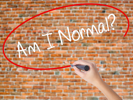 Woman Hand Writing Am I Normal? with black marker on visual screen. Isolated on bricks. Business concept. Stock Photo Stock Photo