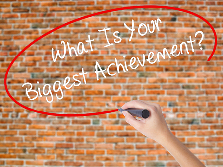 overachieving: Woman Hand Writing What Is Your Biggest Achievement? with black marker on visual screen. Isolated on bricks. Business concept. Stock Photo Stock Photo