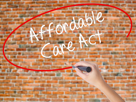 Woman Hand Writing Affordable Care Act with black marker on visual screen. Isolated on bricks. Business concept. Stock Photo Stock Photo