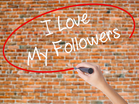 Woman Hand Writing I Love My Followers with black marker on visual screen. Isolated on bricks. Business concept. Stock Photo