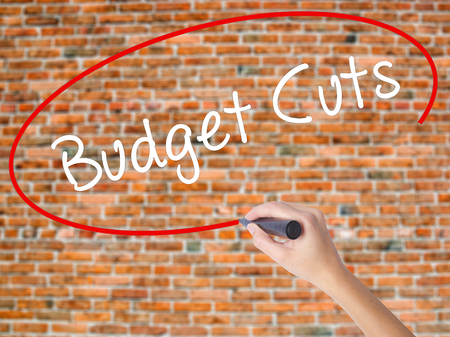 Woman Hand Writing Budget Cuts with black marker on visual screen. Isolated on bricks. Business concept. Stock Photo