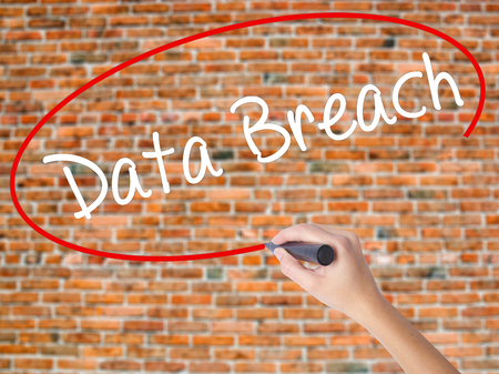 incursion: Woman Hand Writing Data Breach with black marker on visual screen. Isolated on bricks. Business concept. Stock Photo Stock Photo