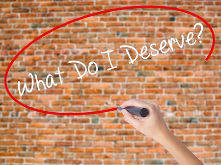 Woman Hand Writing What Do I Deserve? with black marker on visual screen. Isolated on bricks. Business concept. Stock Photo Archivio Fotografico