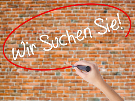 Woman Hand Writing Wir Suchen Sie! (Looking For You in German) with black marker on visual screen. Isolated on bricks. Business,  technology, internet concept. Stock Photo