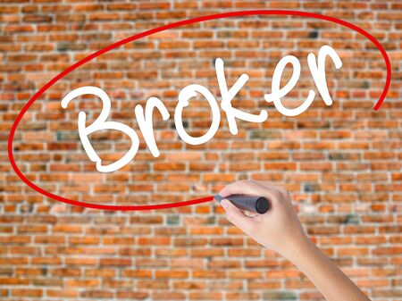 Woman Hand Writing Broker with black marker on visual screen. Isolated on bricks. Business concept. Stock Photo Stock Photo