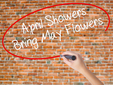 Woman Hand Writing April Showers Bring May Flowers with black marker on visual screen. Isolated on bricks. Business concept. Stock Photo