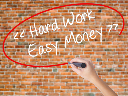 Woman Hand Writing Hard Work - Easy Money with black marker on visual screen. Isolated on bricks. Business concept. Stock Photo Stock Photo