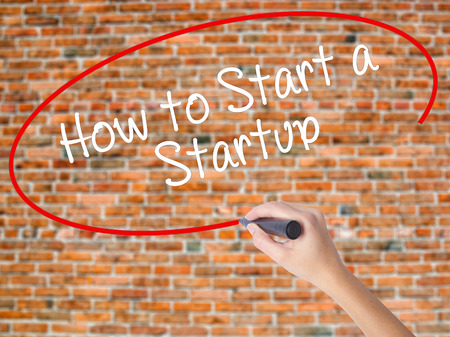 Woman Hand Writing How to Start a Startup with black marker on visual screen. Isolated on bricks. Business concept. Stock Photo
