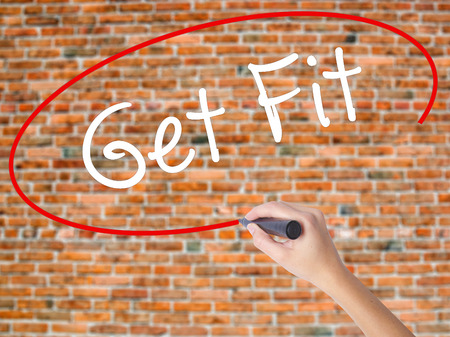 work less: Woman Hand Writing Get Fit  with black marker on visual screen. Isolated on bricks. Business concept. Stock Photo
