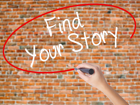 Woman Hand Writing Find Your Story with black marker on visual screen. Isolated on bricks. Business concept. Stock Photo