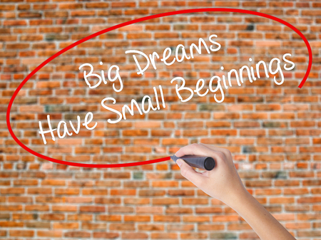 Woman Hand Writing Big Dreams Have Small Beginnings with black marker on visual screen. Isolated on bricks. Business concept. Stock Photo