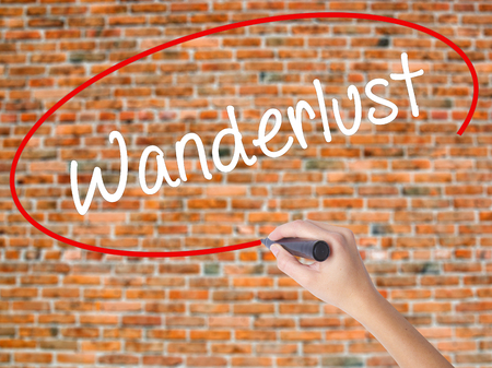 Woman Hand Writing Wanderlust with black marker on visual screen. Isolated on bricks. Business concept. Stock Photo