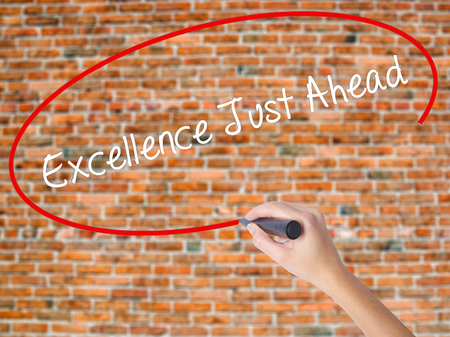 Woman Hand Writing Excellence Just Ahead with black marker on visual screen. Isolated on bricks. Business concept. Stock Photo Stock Photo