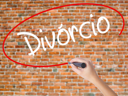 Woman Hand Writing Divorcio (Divorce in Portuguese) with black marker on visual screen. Isolated on bricks. Business concept. Stock Photo