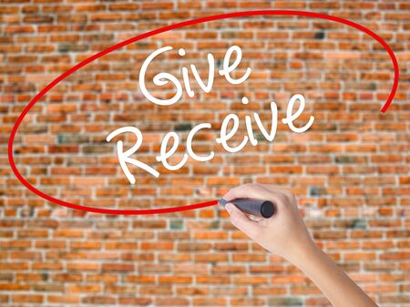 Woman Hand Writing Give Receive with black marker on visual screen. Isolated on bricks. Business concept. Stock Photo Stock Photo