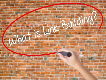 wiki: Woman Hand Writing What is Link Building? with black marker on visual screen. Isolated on bricks. Business concept. Stock Photo