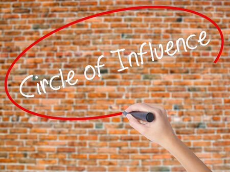 persuade: Woman Hand Writing Circle of Influence with black marker on visual screen. Isolated on bricks. Business concept. Stock Photo Stock Photo