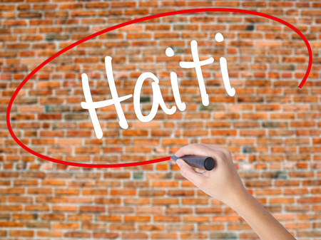 Woman Hand Writing Haiti with black marker on visual screen. Isolated on bricks. Business concept. Stock Photo
